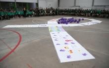 Patio del colegio lleno de niños, lazo de pancartas y globos morados