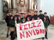 Alumnos en la iglesia con la pancarta de feliz navidad